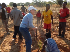 Sue, a member of the mission team, plants moringa with the children.